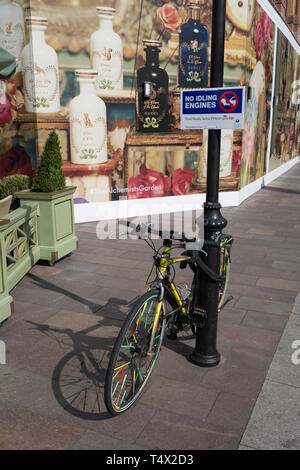 A No Idling Engines sign aimed at waiting black cab drivers, and a locked-up bike at the rear of the Harrods Department Store in Knightsbridge, on 15th April 2019, in London, England. - Stock Image