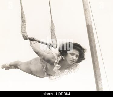 Female trapeze artist in mid-air - Stock Image