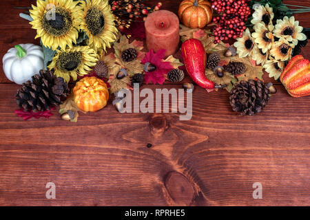 Thanksgiving decor with candle, pine cones, sunflowers, acorns, pumpkins, squash, guard, berries and maple leaves - Stock Image