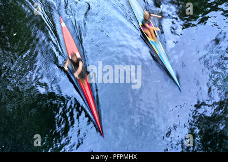 Two kayaks at speed in the water - Stock Image