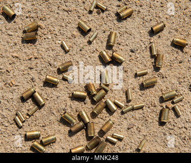 An assortment of spent center fire and rim fire cartridge casings lying in the sand where they fell in a sand pit in the Adirondack Mountains, NY USA - Stock Image