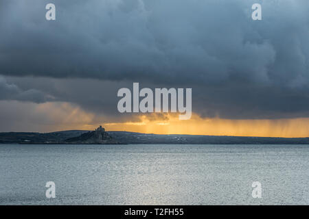 Penzance, Cornwall, UK. 2nd April 2019. UK Weather. The view from Penzance towards Marazion this morning, showing dark storm clouds overhead. Credit: Simon Maycock/Alamy Live News - Stock Image