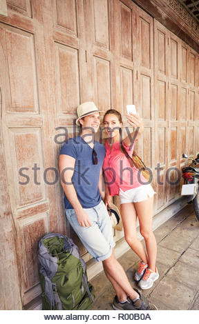 Young couple taking selfie on sidewalk - Stock Image