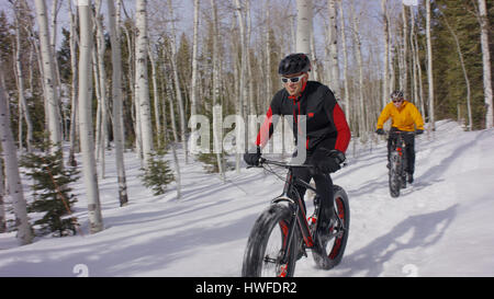 Men riding mountain bikes in remote snowy forest - Stock Image