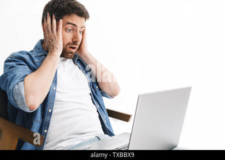 Portrait of a shocked handsome bearded man wearing casual clothes sitting in chair isolated over white background, working on laptop computer - Stock Image