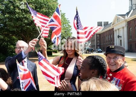 U.S First Lady Melania Trump and Philip May, husband of British Prime Minister Theresa May, wave British and American flags during a visit to the Royal Hospital Chelsea July 13, 2018 in London, United Kingdom. - Stock Image