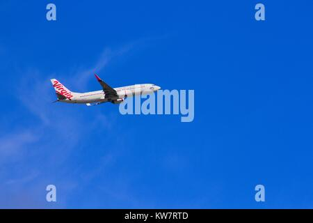 Virgin airliner against a bright blue sky. - Stock Image