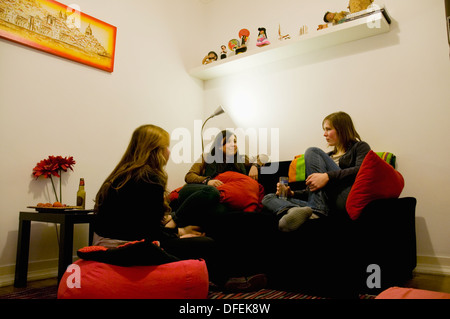 Three female guest relaxing and chatting in one of the common rooms at the Lisboa Central Hostel, Lisbon, Portugal. - Stock Image