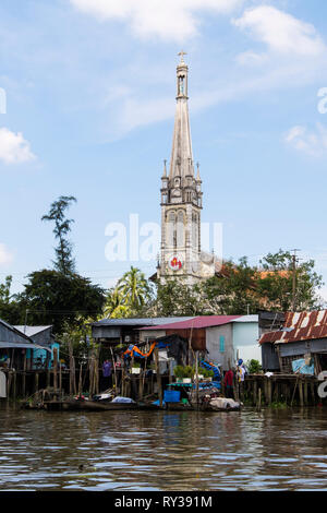 20th century Catholic Cathedral Church behind typical Vietnamese tin shack stilt houses on riverside of Co Chien River in Mekong Delta. Cai Be Vietnam - Stock Image