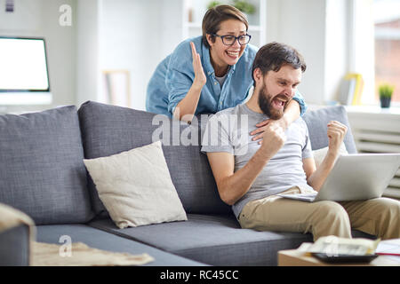 Glad and ecstatic couple expressing triumph while looking at names of winners in lottery on laptop display - Stock Image