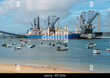 Deep water terminal and silo for grain, derived products and oleaginous products in Trafaria, Portugal with fishing boats near the beach - Stock Image
