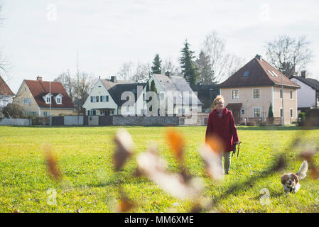 Old woman walking on meadow with pet dog - Stock Image