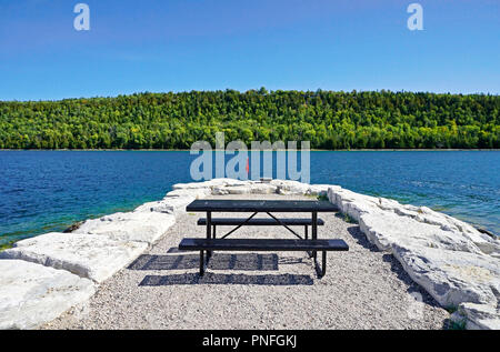 Lush green forest and deep blue water and sky above picnic table on stone pier in Gore Bay, Manitoulin Island, Ontario, Canada - Stock Image