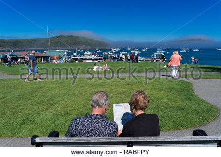 Couple consulting a map of Bar Harbor, Maine, sitting on a bench at Agamont Park . - Stock Image