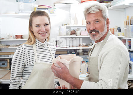 Portrait Of Mature Man With Teacher Looking At Vase In Pottery Class - Stock Image