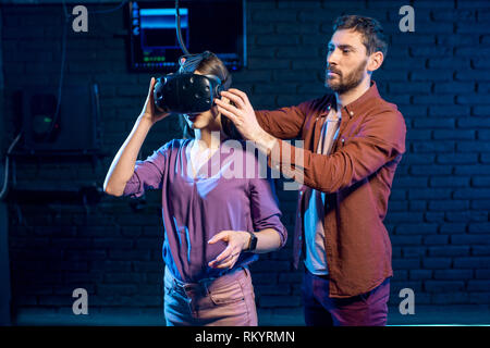 Man helping young woman to wear virtual reality headset prepairing for the game in the playing club - Stock Image