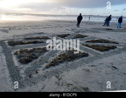 West Wittering Beach Commemorates Armistice DayWest Wittering Estate invited local residents and visitors to join them on Wittering beach to commemorate 100 years since the end of WWI. Inspired by Danny Boyle's 'Pages in the Sea' Ð a national art event Seaweed and raked sand sculpture of the Union Jack. Contributor:  Gary Blake /  West Wittering Estate /Alamy Stock Photo - Stock Image