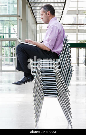 A Caucasian businessman sitting on top of multiple stacked chairs and working on a laptop computer. - Stock Image