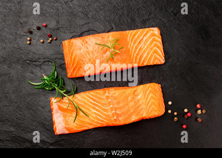 Two slices of raw salmon with rosemary and peppercorns on black - Stock Image