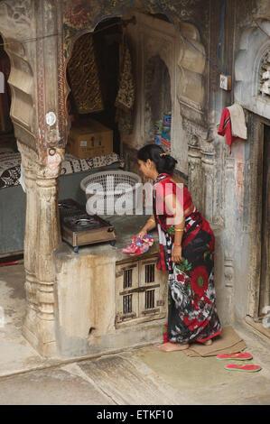 Indian woman cleaning in her kitchen. Mandawa, Shekawati region, Rajasthan India - Stock Image