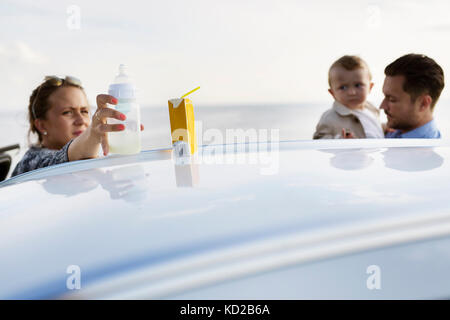 Parents with son (18-23 months) behind car - Stock Image