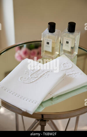 Embroidered cloth and bottles on table - Stock Image