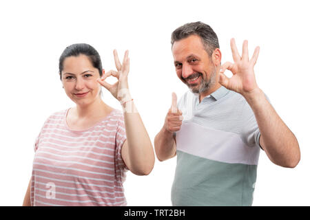 Cheerful couple making thumb up like and okay gesture with fingers isolated on white studio background - Stock Image
