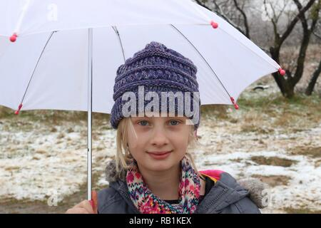 Portrait of a young girl in the snow holding a white umbrella - Stock Image