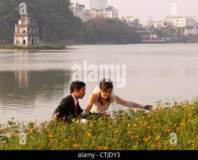 Vietnamese wedding couple posing with the Torttoise Tower in the background, Hoan Kiem Lake, Hanoi Old Quarter, - Stock Image