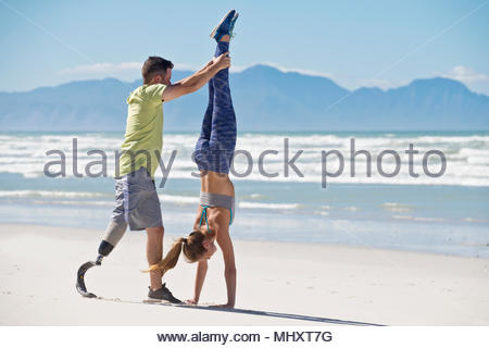 Man Wearing Prosthetic Blade Helping Woman To Do Handstand On Beach - Stock Image