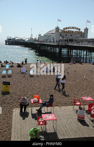 Brighton, UK - September 1 2018: People bask in the sun on the pebbles beach by Brighton's  Palace Pier on 1​ September 2018.   The Pier, in the central waterfront section, opened in 1899 houses amusment rides as well as food kiosks .Credit: David Mbiyu Credit: david mbiyu/Alamy Live News - Stock Image