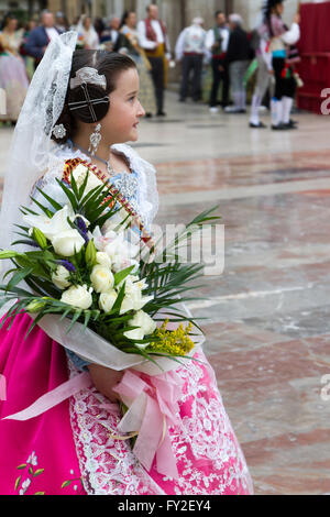 Girl bringing flower offering at the offering to the Holy Lady of Valencia Spain - Stock Image