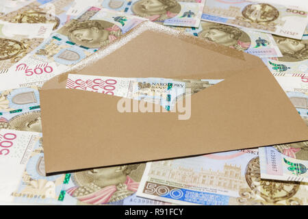 Brown envelope with 500 PLN banknotes on banknotes background - Stock Image