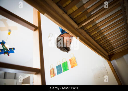 Boy looking down from the bunkbed, Munich, Germany - Stock Image