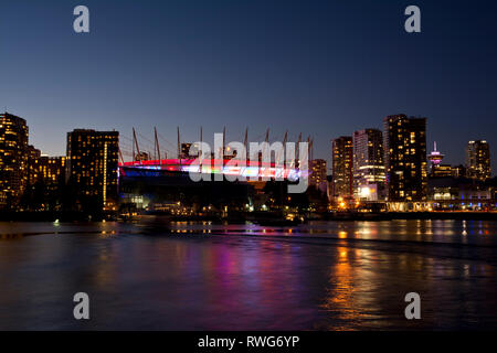 BC Place Stadium and Vancouver city skyline on False Creek.  BC Place is lit with international flags for the Canada Sevens rugby tournament 2019. - Stock Image