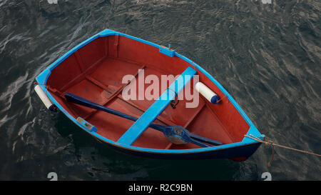 Small wooden fishing boat with a single blue oar inside, tied up near a pier isolated against dark, murky ocean water in Los Abrigos, Tenerife, Spain - Stock Image