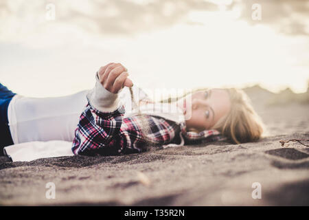 Hipster young cute blonde caucasian girl play with the sand at the beach - lay down people in vacation leisure activity - golde sunset in background w - Stock Image