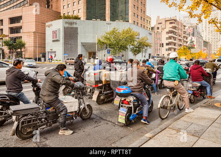 28 November 2018: Shanghai, China - Electric scooters, mainly used by couriers and messengers, wait at traffic lights in central Shanghai. - Stock Image