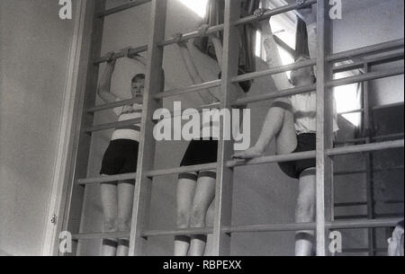 1950s, historical, schoolgirls in gym clothes at a County Secondary school on an indoor wooden climbing frame at a PE class, England, UK. - Stock Image