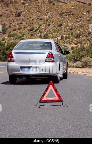Warning triangle sign near breakdown car on road - Stock Image