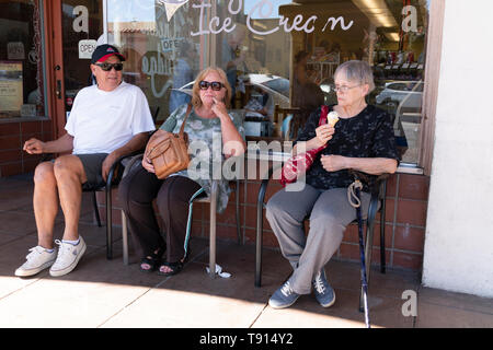 Three adults, one older male and two females sit outside an ice cream shop in Ojai, California. The oldest females eats an ice cream cone. - Stock Image