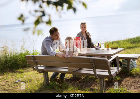 Parents with son (18-23 months) sitting by picnic table - Stock Image