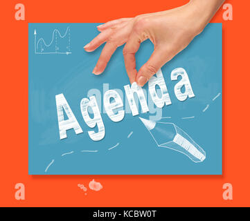 A hand picking up a Agenda concept on a colorful drawing board. - Stock Image