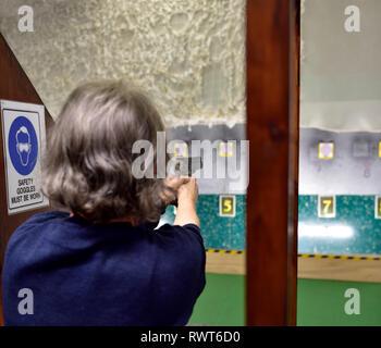 Woman in UK at indoor pistol range aiming at target - Stock Image