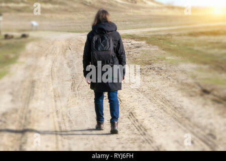 Caucasian woman in black coat arms raised on empty road towards sunset horizontal - Stock Image