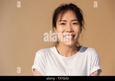 Portrait closeup of amazing chinese girl wearing basic t-shirt smiling and looking at camera isolated over beige background in studio - Stock Image