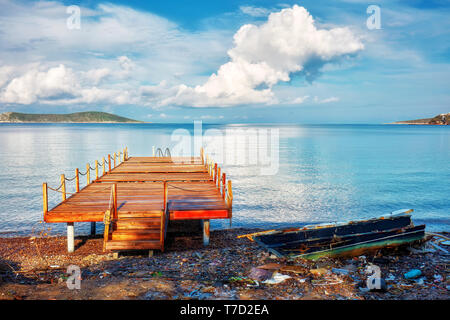 Pier and a stranded boat wreck beached on the sea shore in Cukurbuk bay gumusluk, Bodrum, Turkey. - Stock Image