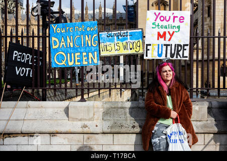London, UK. 23 March 2019. Young woman in front of posters on the rails of the Houses of Parliament. Remain supporters and protesters take part in a march to stop Brexit in Central London calling for a People's Vote. - Stock Image