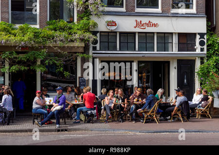 Young people sitting and drinking outside Libertine Cafe in Amsterdam, Netherlands - Stock Image