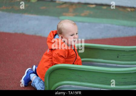 Baby Boy With Orange Raincoat Climbing Up On Slide, Close Up Portrait View - Stock Image